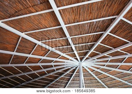 Summer sunshade on beach, near mediterranean sea. White wooden construction with cane roof