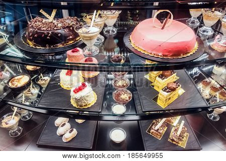 Different desserts on bakery shop-window. Sweets and cakes for every taste