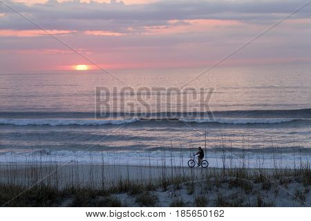 A man bicycles on the beach at he first blush of dawn watching the sun rise through pink clouds as distant pelicans soar out on the sea