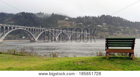 A well placed bench sits on the waterfront with a view of the bridge crossing