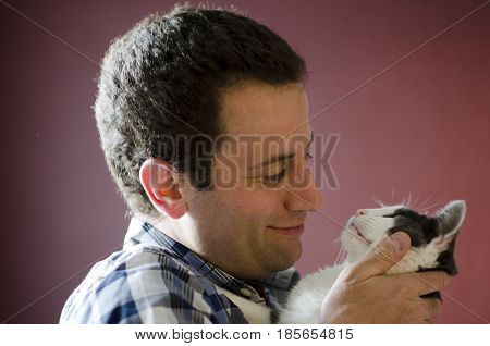 Side view of man and his cat gazing into each other's eyes.