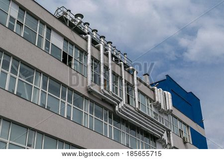 A large number of metal aluminum pipelines are fixed on the facade of the building where there are many windows. The facade of an industrial building with ventilation chimneys.