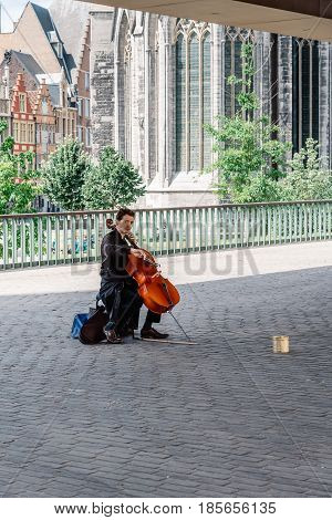 Ghent Belgium - July 31 2016: Musician playing cello under the Stadshal in Ghent. The construction was part of the city project to redevelop the squares and public spaces in historic city center.