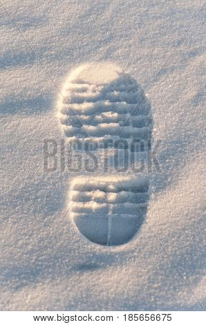 trace from a men's boot and the drawing of a sole on white snow close up with easy shadows