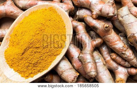 Closeup top view turmeric powder and turmeric roots on old wood background spa beauty skin care concept
