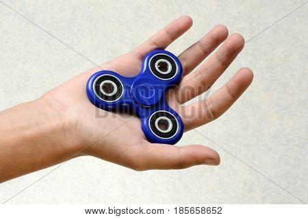 Blue Hand spinner fidgeting hand toy on child's hand
