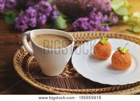 Spring and fresh breakfast on a wooden table. On the table are lilacs cakes and a cappuccino. A bouquet of lilac on a wooden table.