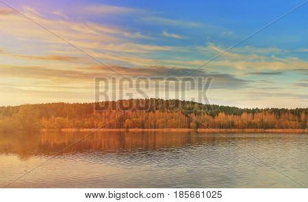 Enchanting landscape of nature on a lake at sunset. Solar side beams, beautiful sky with clouds, colorful landscape.