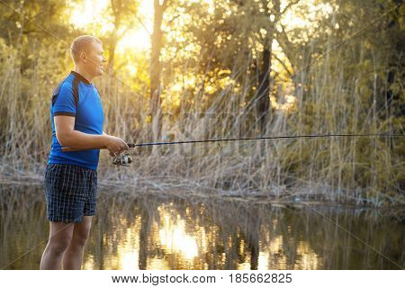 Fisherman with a spinning rod catching fish on a river. Man on a weekend.