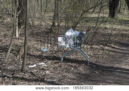 MOSCOW RUSSIA APRIL 30. 2017: Shopping cart with litter in a city park Sokolniki. Plastic litter - biggest problem for environment in modern cities