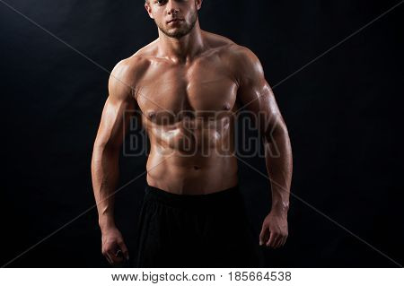 Horizontal cropped studio portrait of a confident young athletic man posing shirtless showing off his six-pack on black background copyspace fitness sexy hot masculinity macho fit model sportsman concept.