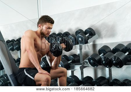 Handsome young man with stunning sexy hot body with full six pack standing at the gym holding dumbbells looking confidently to the camera copyspace naked shirtless masculinity sportsman athlete.