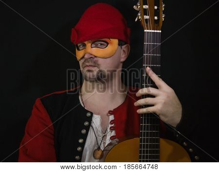 Man in a renaissance mask dressed minstrel suit with guitar