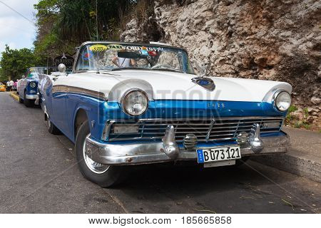 Havana Cuba - January 21 2017: Old american car on the road Old Havana Cuba.Thousands of these cars are still in use in Cuba and they have become an iconic view and a worldwide known attraction