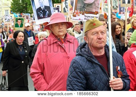 KURSK RUSSIA - May 92017: People in the crowd participating in Immortal Regiment procession in Victory Day. Thousands of people marching toward the Red Square with flags and portraits. Close-up view.