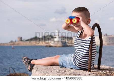 Funny little boy in a sailor stripes vest and shorts looking into the distance through colorful binoculars sitting on a concrete breakwater against the background of the ocean and coast with lighthouse