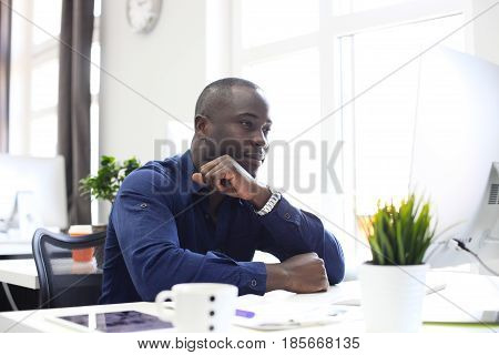 Portrait of a happy African American entrepreneur displaying computer in office