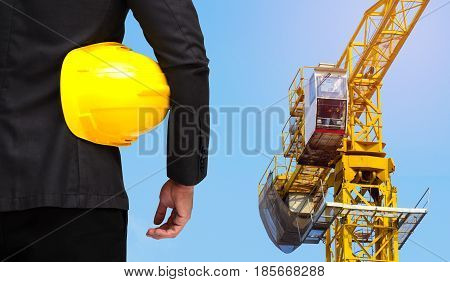 back view of businessman with yellow safety helmet business industrial concept on yellow construction tower crane with blue sky background.