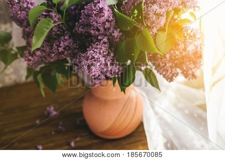 Bright lilac. A bouquet of purple lilacs in a vase near the window. Lilac in a vase. Place for text. Soft focus.