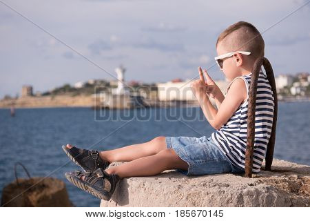 little boy in a vest and shorts sitting on a breakwater on the background of the sea and the shore with a beacon lifting two fingers up