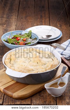 Homemade meat pie from puff pastry with beef and vegetables on wooden table Copy space