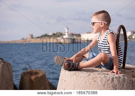 beautiful little boy in sunglasses and sailor stripes vest and shorts sitting on a concrete breakwater against the background of ocean and the shore with lighthouse