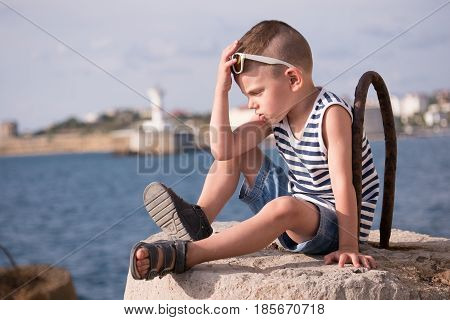 thinking little boy in sunglasses and sailor vest sitting on breakwater against sea and shore with lighthouse