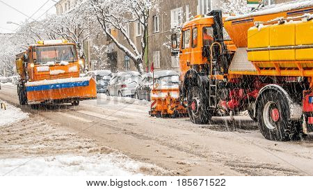 snow plough making shovelling roads in european city during winter storm