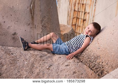 smiling little boy in a vest and shorts lies on a concrete breakwater in port