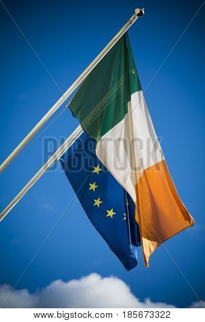 Irish and European Union flags together against blue sky