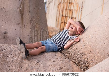 smiling little boy in a vest and shorts lies on a concrete breakwater in port covering his eyes with his hand
