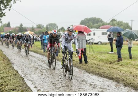 Ennevelin France - July 092014: The peloton riding on a cobblestone road during the stage 5 of Le Tour de France 2014.