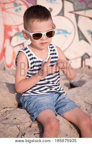 cute little boy in singlet and shorts pulls out a splinter from his finger sitting in front of wall with graffiti