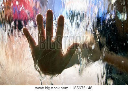 A hand pressed to the glass, with a stream of waterfall on the surface of the glass. Water flows through the glass, Glass closeup. Abstract background blurred by water flows