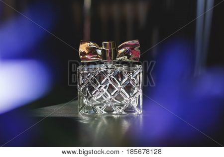 stylish bottle of female perfume over blue