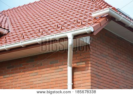 Close up on House Problem Areas for Rain Gutter Waterproofing Outdoor. Home Guttering Roofing Construction Gutters Plastic Guttering System Roof Tiles Guttering & Drainage Pipe House Building.