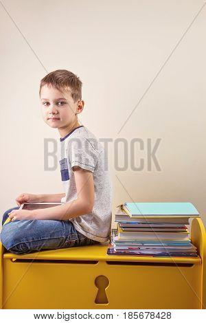 Kid using digital tablet sitting near bis stack of books