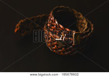 Brown belt with cuff on black background