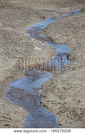 Meandering water stream flowing through a dry pond.