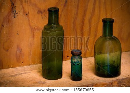 Still Life with differently shaped glass bottles on an old drugstore shelf.