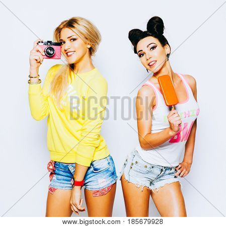 Bright summer portrait of two cheerful girlfriends, blonde and brunette. Having fun, enjoying ice cream and taking pictures with a vintage camera. Bestis. Indoor. Eskimo.