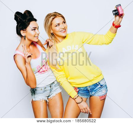 Two girls taking self image together on pink vinage camera, indoor. Close up lifestyle portrait of girlfiends makes funny grimaces. Bestis. Indoor.