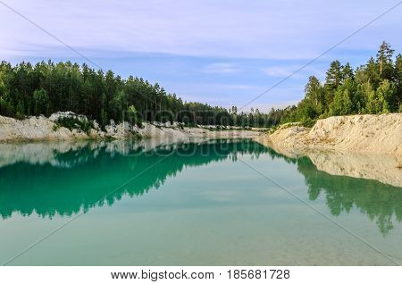 Blue summer waters of kaolin quarry in Kyshtym Southern Urals Russia- summer water landscape. Colorful summer water background. Summer nature in cloudy weather. Summer landscape view of turquoise quarry water and summer trees