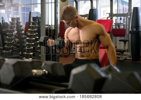 Young fair handsome bodybuilder exercising with a dumbell in a gym