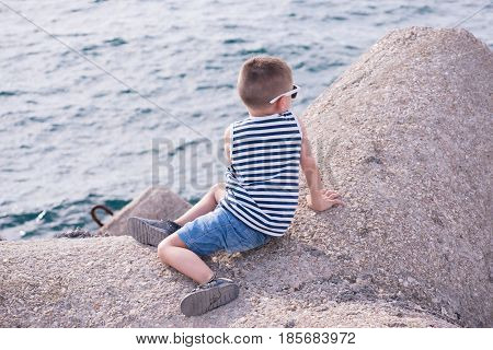 healthy little boy dressed in a striped shirt and denim shorts sitting on concrete breakwater by the sea