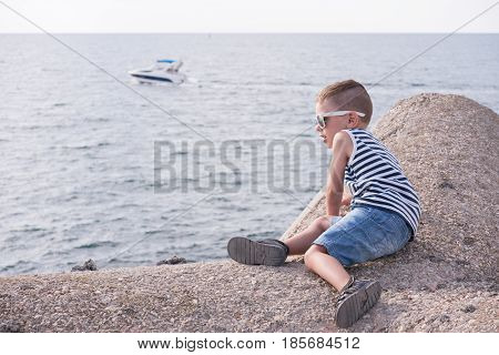 Little boy with sunglasses and striped vest sitting on concrete breakwater in front of the sea with floating boat
