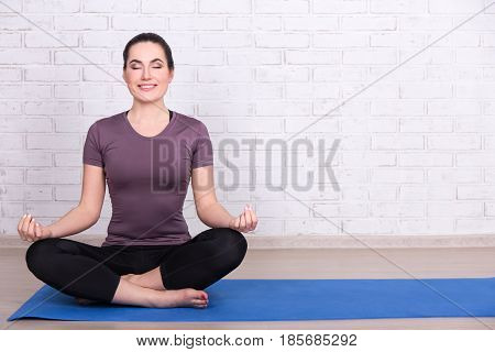 Slim Sporty Woman Sitting In Yoga Pose On Mat Over White Brick Wall