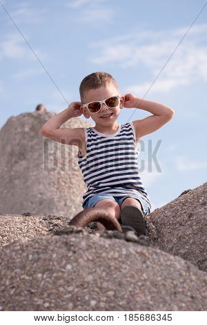 Cute smiling little boy in sunglasses and singlet sitting on a concrete breakwater