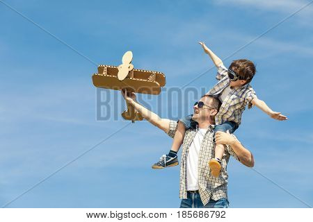 Father And Son Playing With Cardboard Toy Airplane In The Park At The Day Time.