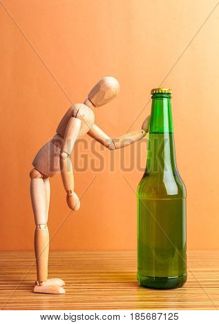 Alcoholism concept. Wooden doll with Alcohol drink